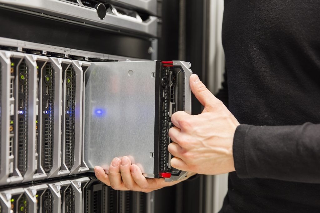 It engineer or consultant working with blade server installation in data rack. Shot in enterprise datacenter.