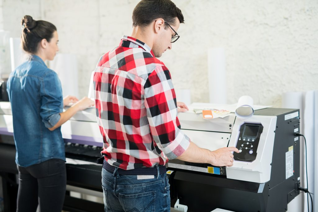 Coworking man and woman in typography office using printing machine while working in team